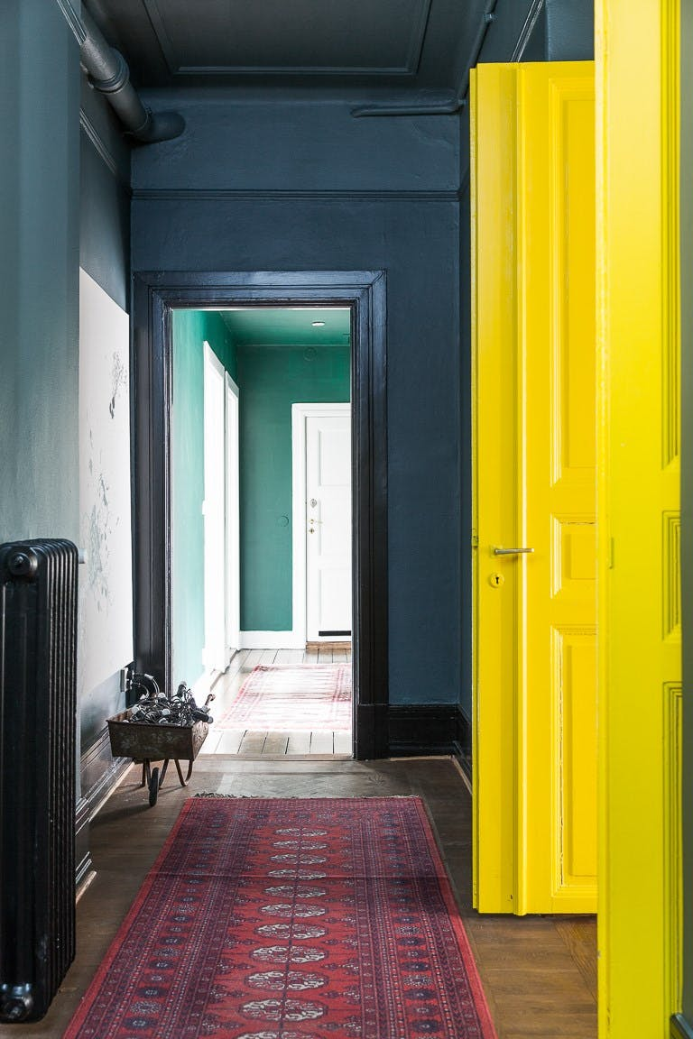 Beautiful, subtle baseboard and panel mould in an forest green hallway with a gorgeous bright yellow door. Image Source: Apartment Therapy.