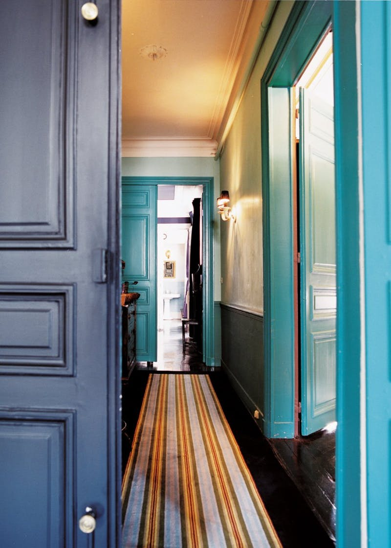 Beautiful chair rail and ceiling treatment in a cool-toned Art Deco hallway. Image Source: Apartment Therapy.