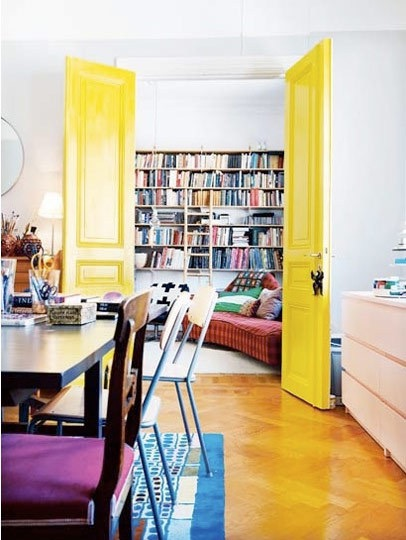 Gorgeous, three-panelled doors painted in a vibrant yellow makes a door-stopping statement as it contrasts with clean, white casing. Image Source: Apartment Therapy.