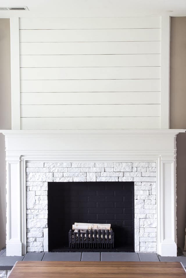 Ceiling-High, fireplace treatment made with tongue and groove or shiplap for a minimalistic style. Image Source: Apartment Therapy.