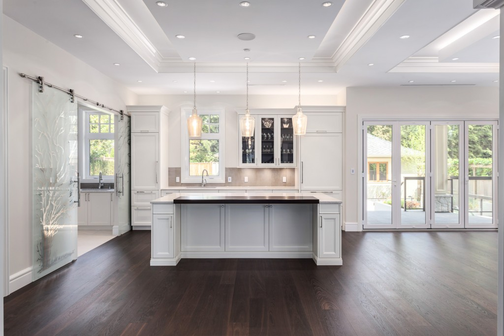 The island in this Haebler Group designed kitchen is framed by the very detailed ceiling, offering an anchoring point for the eye along with function.