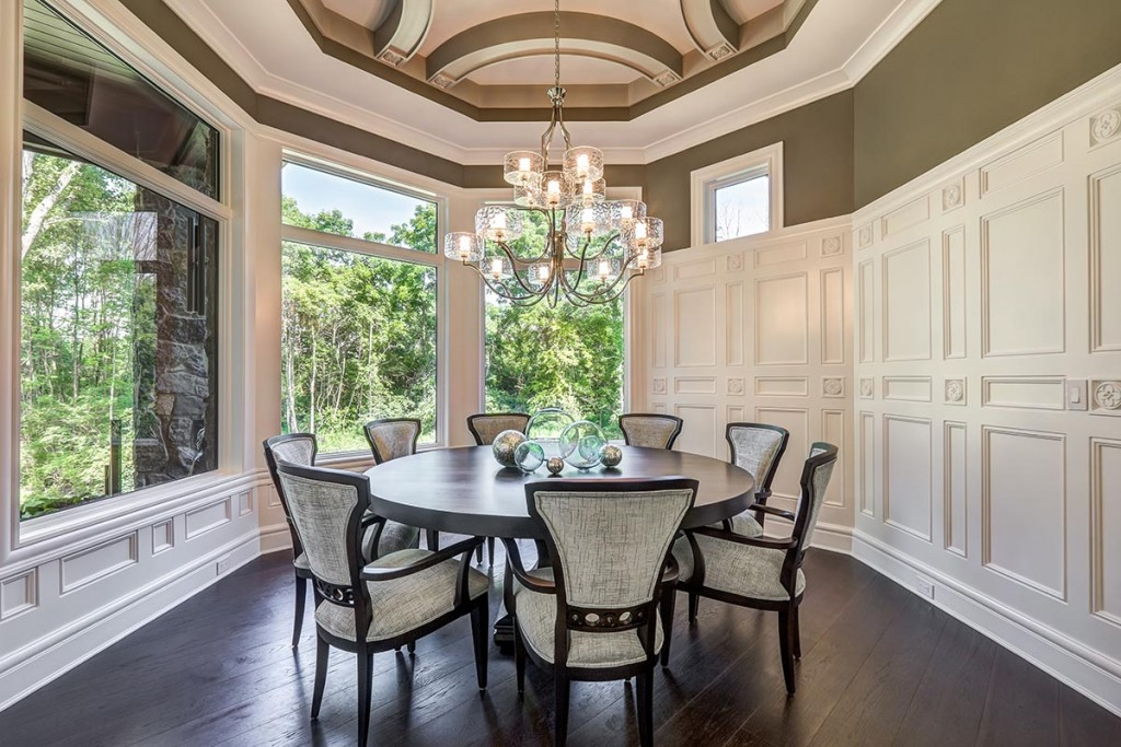 G.A White pairs tall wainscoting with bold ikons for a unique look in this dining room!