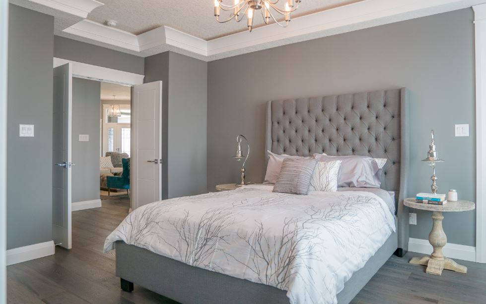 These four panel double doors from Metrie's Very Square Collection elevate the ambiance of this gorgeous bedroom designed by Harmony Builders.