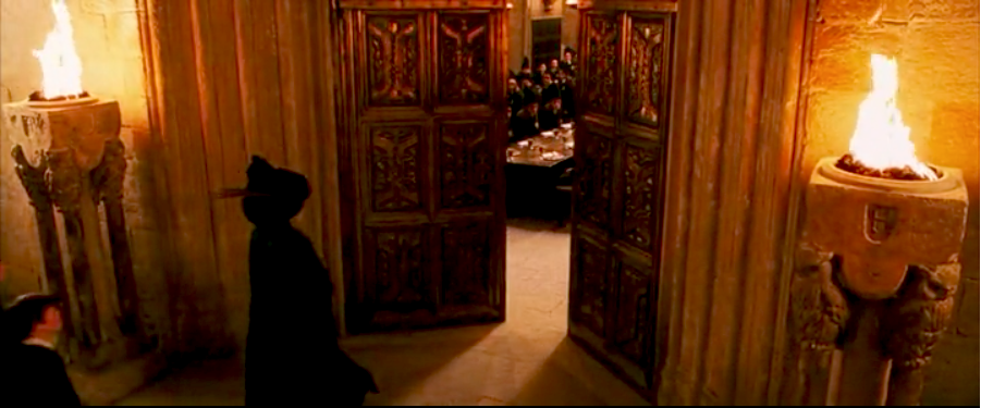 Opulent and regal interior doors leading the characters into Hogwarts' Great Hall.