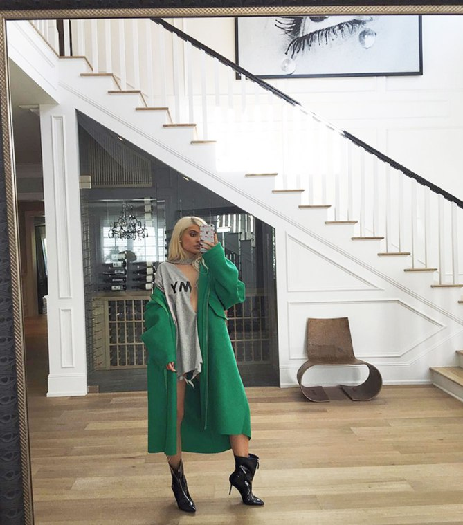 Kylie Jenner snaps a fashionable photo in front of her grandiose staircase embellished in interior finishings.