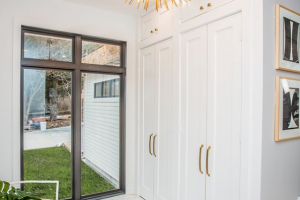 Metrie's True Craft doors are used to create a lovely built-in closet paired with gold hardware