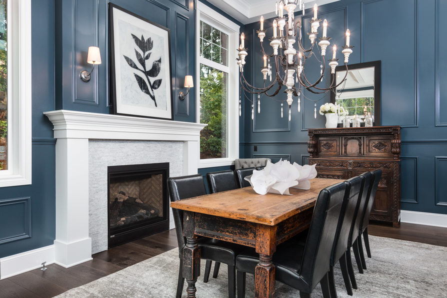 Crisp blue and white are perfectly contrasted in this dining room with stunning window and fireplace accents.