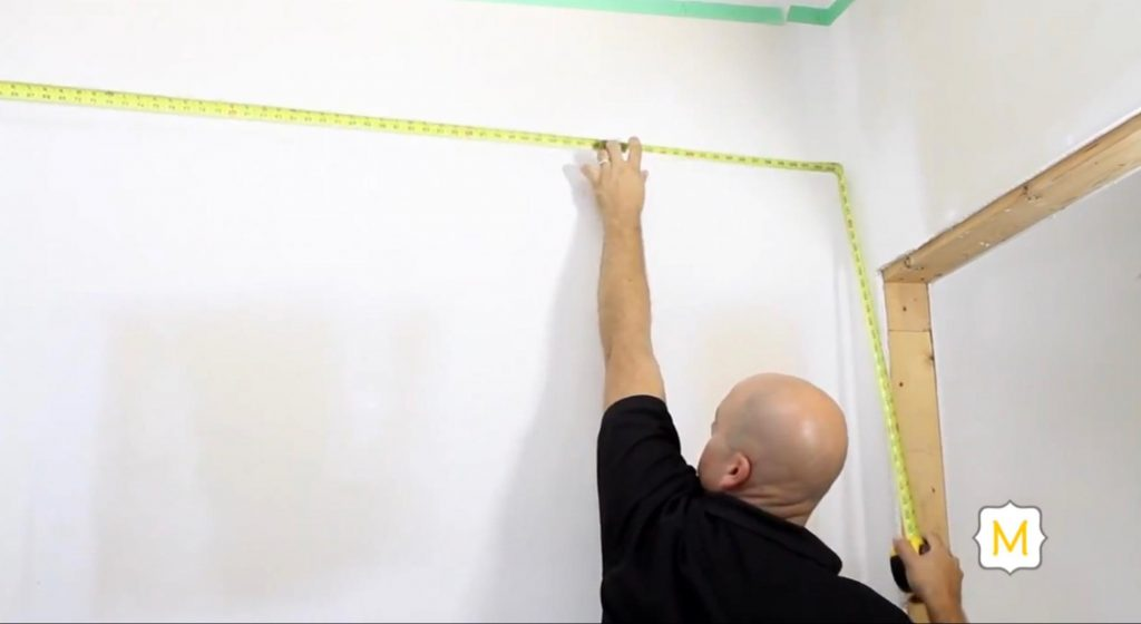 A Man Measures a Wall Before Adding Trim