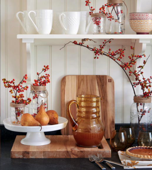 Kitchen counter with two cutting boards, a glass pitcher and a pie, and white shelf holding white mugs, two bowls and berries in glass jars.