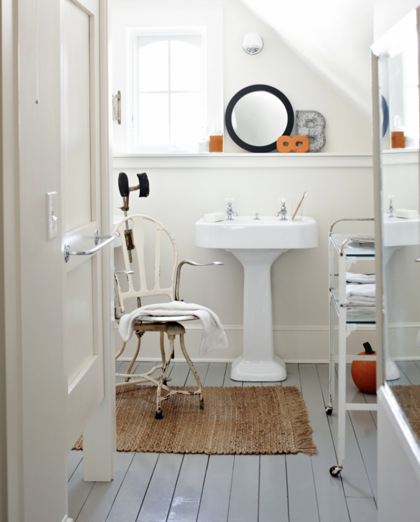 A bathroom with a white sink, shag rug, white chair, rolling cart, orange pumpkin on the floor and a towel sitting on the chair.