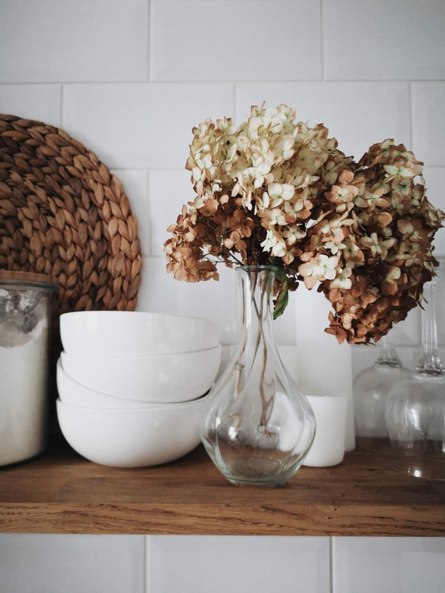 A wooden shelf holding dried hydrangeas, white bowls, a container of flour, wine glasses and a rattan bowl.